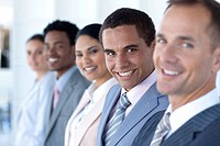 Attractive businessman in a row with his team smiling at the camera