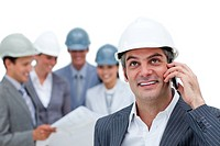 Confident male architect on phone standing in front of his team