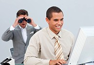 Charimastic businessman looking his colleague´s computer through binoculars in the office