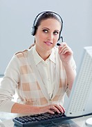 Pensive businesswoman working at a computer with headset on in the office