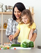 Beautiful mother helping her daughter cut vegetables in the kitchen