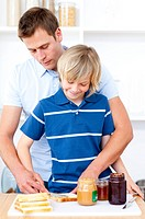 Adorable boy and his father preparing breakfast in the kitchen
