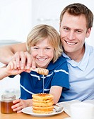 Happy boy and his father putting honey on waffles in the kitchen