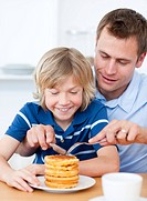 Attentive father and his son eating waffles in the kitchen