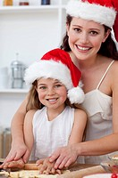Smiling mother and daughter baking Christmas cakes in the kitchen