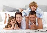 Happy family lying in bed and using a remote