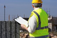 middle aged grey haired man wearing hard hat and hivis vest holding a clipboard building blocks on construction building site in northern ireland uk