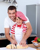 Father and son cutting bread in kitchen