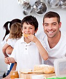 Father and son eating a toast in breakfast time in the kitchen