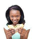 Joyful young woman eating a sandwich against a white background