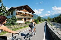 Cyclists leave the mediaeval walled town of Glurns in the Alto Adige region of Italy  Riverside chalet on the Via Lungo Adige