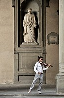 Florence, Italy  Street musician plays classical violin under statue of city father Cosimo de Medici  Outside the Uffizi Gallery