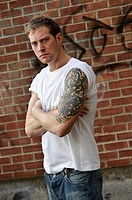 30 year old man standing alone with heavily tattooed arms