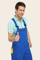 Man in overall showing thumbs up sign, smiling, portrait