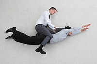 Two businessmen, one of them flying, the other sitting on his back, side view, elevated view, portrait