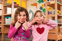 Germany, Two girls 4_5, 6_7 in nursery making faces, portrait, close_up