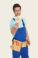 Man wearing tool belt holding currency, smiling, portrait
