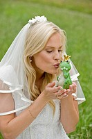 Bride kissing toy frog.