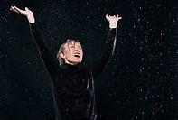 Woman enjoying in rain, arms up.