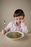 A boy looking disappointedly at a bowl of vegetable soup