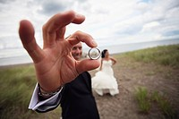 a bride and groom standing on a dirt road and the groom is holding his wedding band