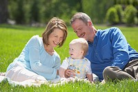 parents sitting on the grass with their young son