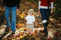 a family walking on a path in autumn