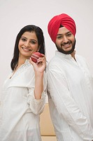 Woman with Sikh man holding cricket ball and smiling