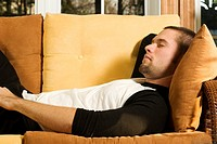Young man having a nap on couch in living room