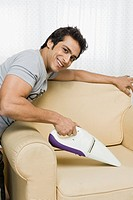 Man cleaning sofa with a vacuum cleaner