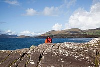 county kerry, ireland, a couple sits overlooking the water near caherdaniel
