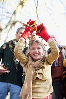 Laughing girl throwing autumn leaves