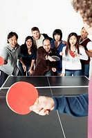 One man facing group of table tennis players