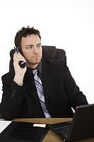 Caucasian businessman setting at a desk talking on the phone