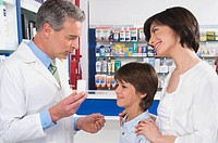 Pharmacist talking with a boy and his mother