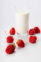 Close_up of a glass of milk and strawberries