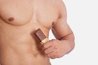 Mid section view of a man holding a protein bar