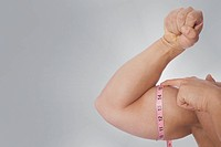 Man measuring his biceps with a tape measure