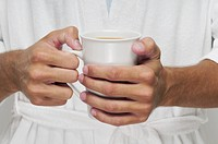 Mid section view of a man holding a cup of coffee