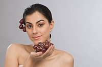 Portrait of a woman holding a bunch of red grapes