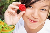 Woman holding a strawberry and smirking