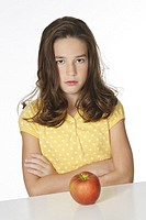 Cute Caucasian girl unhappy about eating an apple