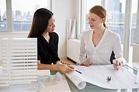 Businesswomen looking at blueprints