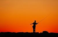 Boy fishing from a jetty at sunset, Menemsha, Martha´s Vineyard