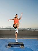 Woman doing step aerobics