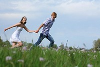 Young couple walking in summer landscape