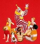 Clown reading book to group of children and one dog