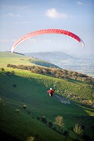 England, East Sussex, Sussex Downs. A lone paraglider soars above Devils Dyke on the East Sussex Downs.