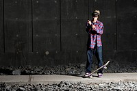 Skateboarder fixing his cuff with board at feet