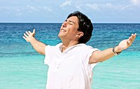 man at the beach with his arms open enjoying his freedom while on vacation